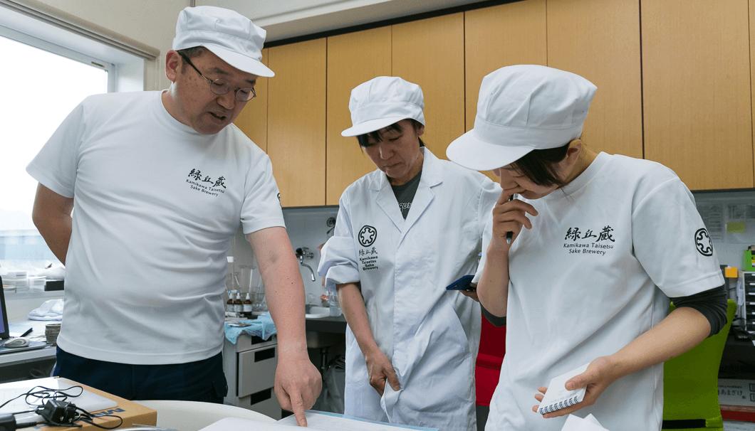醪の温度管理について、川端杜氏からのアドバイスを受ける亀井さん(写真中央)と吉田さん(同右)