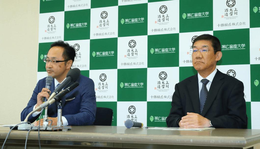 塚原社長と奥田学長が並ぶ写真