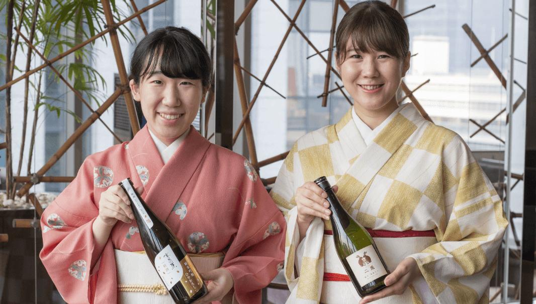 若い女性唎酒師ふたりが日本酒ボトルを持って立つ姿