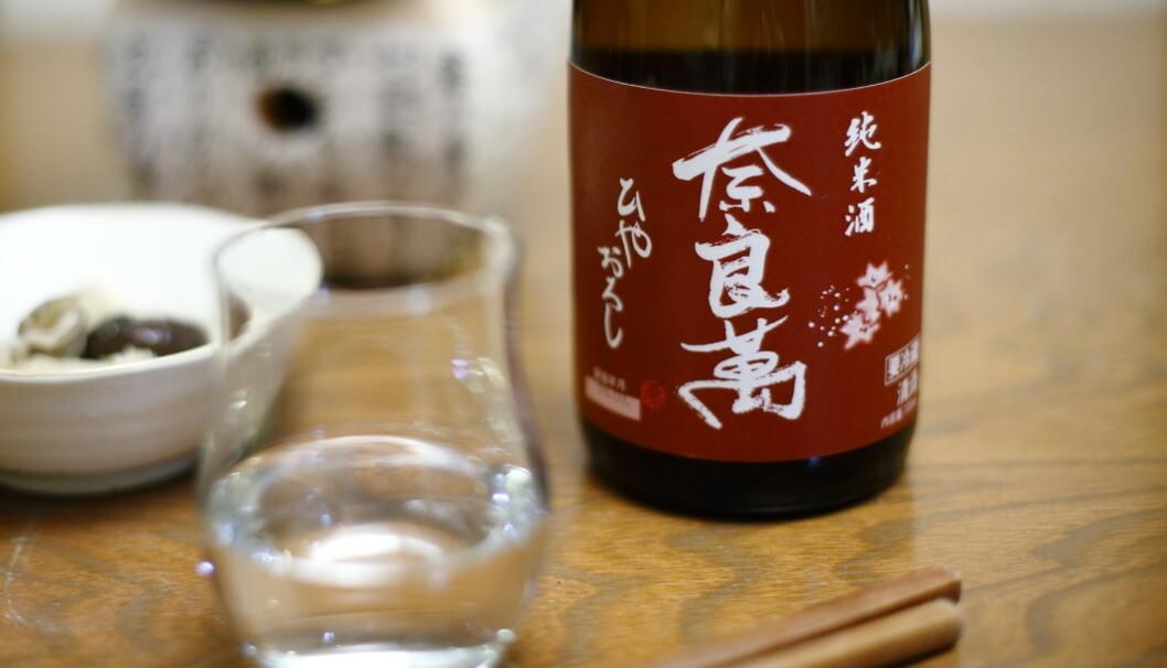 グラスに注がれた奈良萬と、そのボトル
