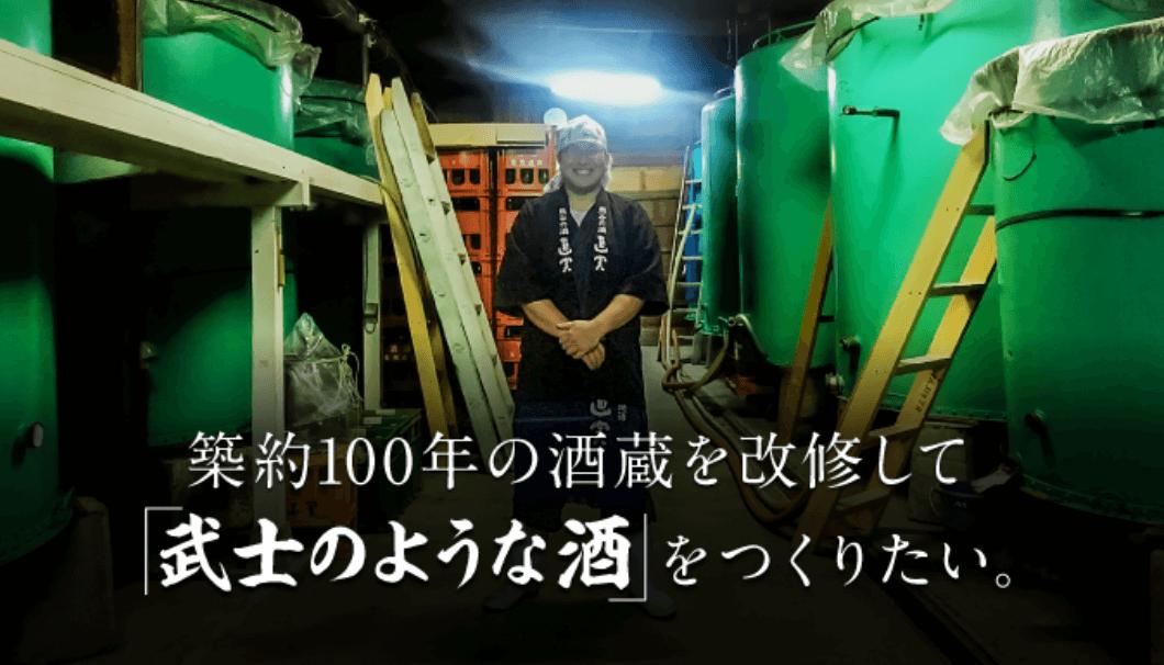 権田酒造の七代目蔵元が、タンクの前で笑顔の写真