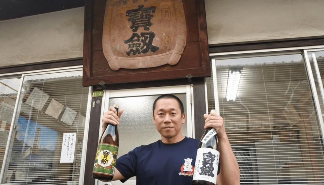 宝剣レトロラベル、宝剣純米 を両手に持つ土井さん