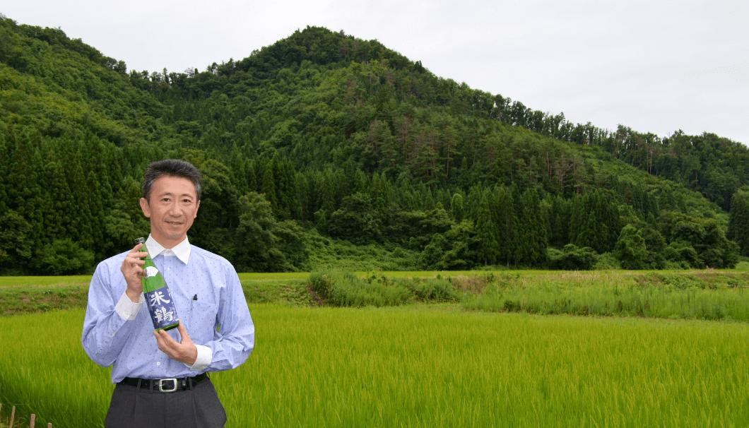 蔵元の梅津陽一郎さん。後ろに広がるのは、米鶴酒造の自社田